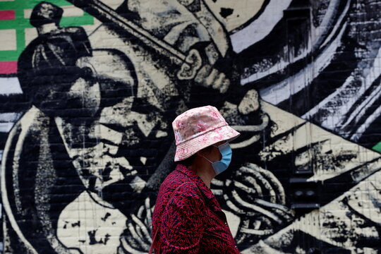 A woman wearing a protective face mask walks by a mural following the May 31, 2021 unprovoked attack on a 55 year old Asian woman, in Manhattan's Chinatown district of New York City