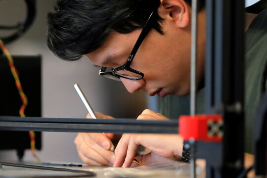 Print service manager Leonardo Chiang works on a large format FDM 3D printer at gCreate, a 3D printer manufacturer, in New York City