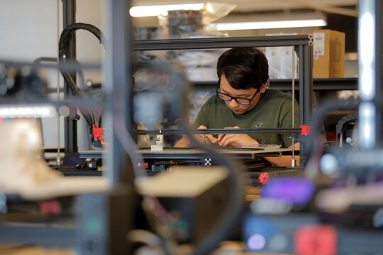 Print Service Manager Leonardo Chiang works on a large format FDM 3D printer at gCreate, a 3D printer manufacturer, located in Brooklyn, New York City