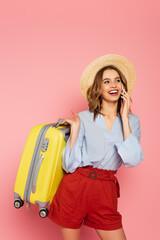 Fototapeta Pretty tourist with suitcase talking on smartphone on pink background obraz