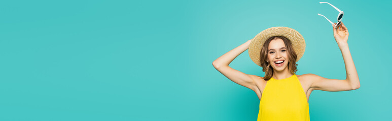 Positive woman with straw hat and sunglasses isolated on blue, banner