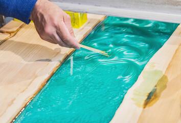 Fototapeta carpenter mixes epoxy to create a tracery on the kitchen table obraz