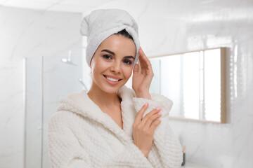 Obraz Happy young woman with towel on head in bathroom. Washing hair - fototapety do salonu