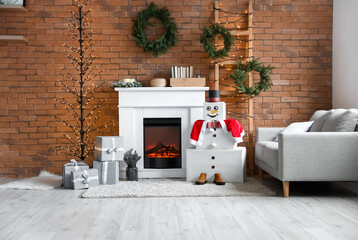 Obraz Interior of living room with fireplace and decorative snowman - fototapety do salonu