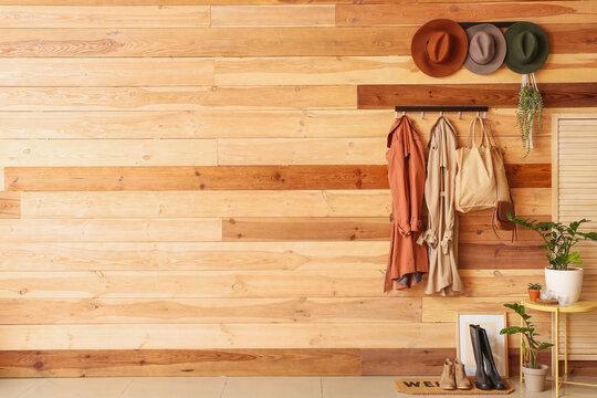 Hangers with clothes and hats on wooden wall