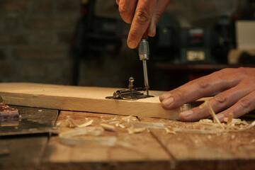 Obraz Carpenter screwing metal chrome hinges on wooden plank in the workshop. - fototapety do salonu