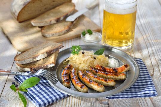 Nürnberger Rostbratwürste mit Kraut und Meerrettich traditionell auf dem Zinnteller serviert  - Fried Bavarian sausages from Nuremberg with sauerkraut and horseradish served on a pewter plate