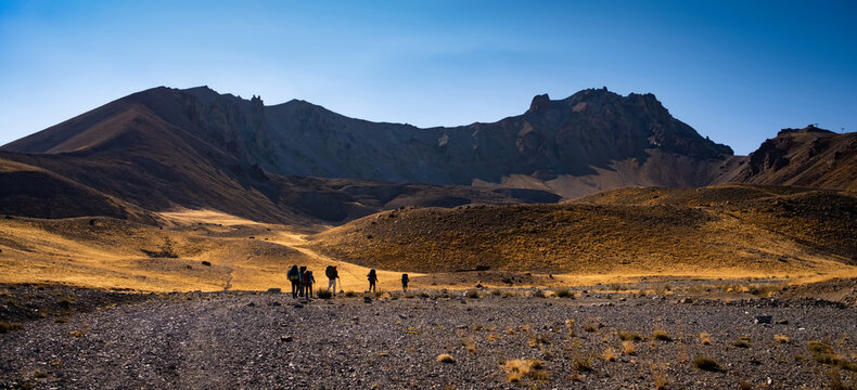 Hiking on volcano Erciyes in Turkey in sunrise time. People with backpacks climbing to the top of mountain surrounded beautiful hills. Scenery Kayseri landscapes with blue sky
