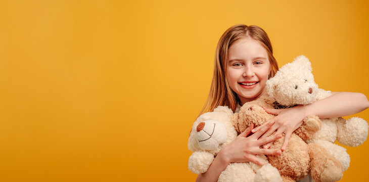 Beautiful girl child with three teddy bears in her hands isolated on yellow background with copyspace. Horizontal portrait of kid holding toys and smiling looking at the camera