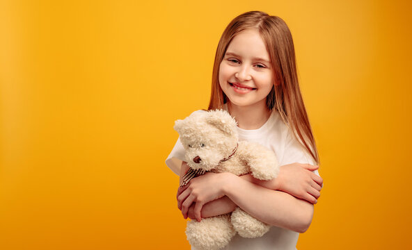 Beautiful little girl child hugging teddy bear and smiling isolated on yellow background with copyspace. Horizontal portrait of kid holding toy and looking at the camera
