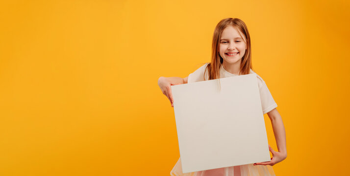 Beautiful girl child holding white canvas and looking at the camera isolated on yellow background with copyspace. Horizontal portrait of kid holding linen with place for text and smiling