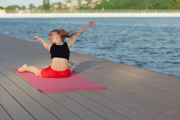 Fototapeta Beautiful young slim girl doing yoga or gymnastic exercise by the lake. Healthy lifestyle. Enjoyment of nature, freedom. Life after quarantine. obraz