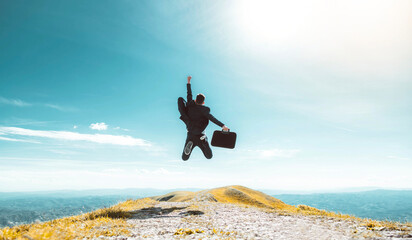 Fototapeta Excited young businessman jumping keeping arms raised hiking the mountain peak - Celebrating success, winner and leader concept obraz