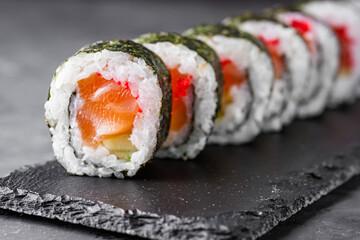 Fototapeta appetizing sushi roll maki with salmon on a black stone plate obraz