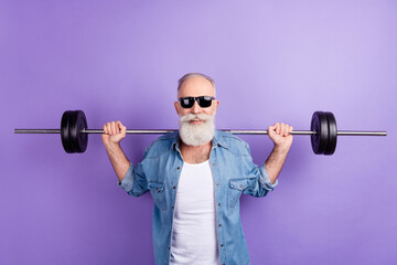 Photo of aged sporty man training intense muscles arms barbell isolated over violet color background - fototapety na wymiar