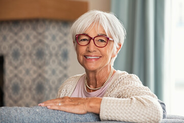Obraz Happy senior woman wearing red spectacles at home - fototapety do salonu