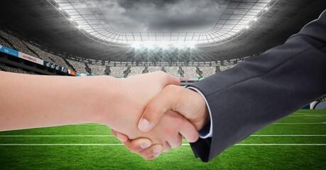 Composition of businesswomen shaking hands over sports stadium