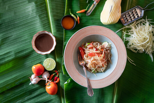 """""""Somtum"""" in Thai on  table  .green papaya salad in plate  on banana leaves  background .Thai Food Concept. Top View"""