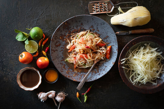 """""""Somtum"""" in Thai on  table  .green papaya salad in plate on old kitchen table background .Thai Food Concept. Top View"""