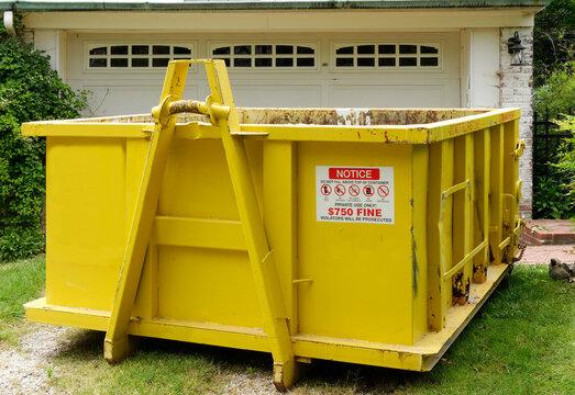 Yellow industrial dumpster in residential neighborhood.