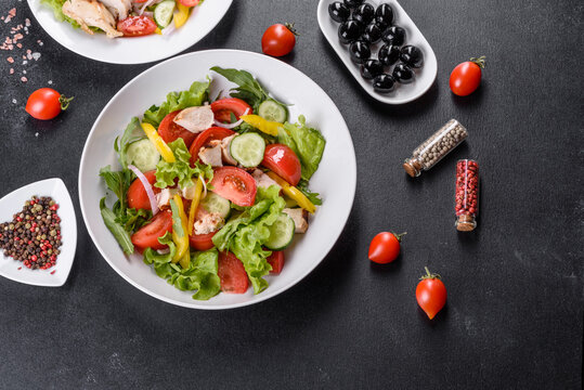 Fresh delicious salad with chicken, tomato, cucumber, onions and greens with olive oil
