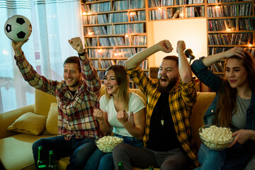 Obraz Friends watching football game at home and drinking beer while relaxing on the couch - fototapety do salonu