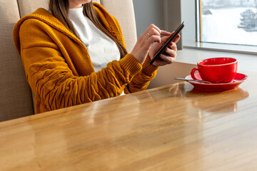 Young woman in orange colored cardigan is reading electronic book on Ebook reader in cafe.