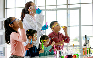 Obraz Asian female scientist teacher in white lab coat having fun playing blowing soap bubbles with little innocent happy pre-elementary boy and girl children wears safety goggles in school laboratory - fototapety do salonu
