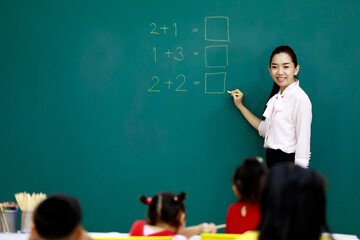Fototapeta Portrait shot of Asian beautiful female mathematic tutor standing smiling holding chalk writing elementary school math equation questions on chalkboard while group of boy and girls students studying obraz