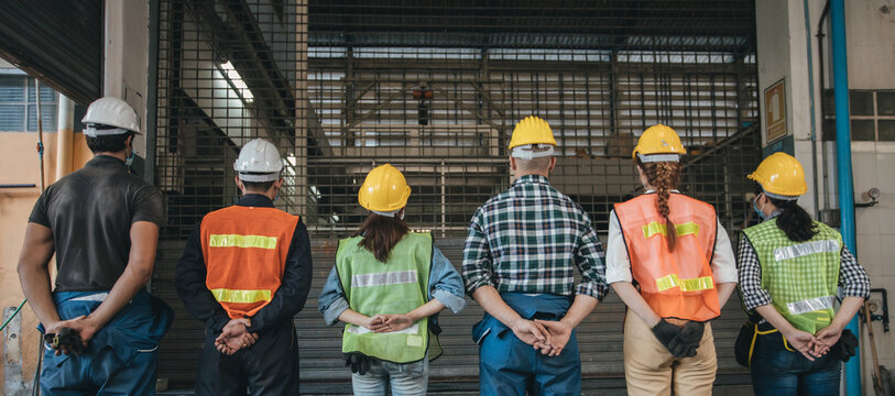 group of industrial worker wearing protective in factory. view from the back, group of workers