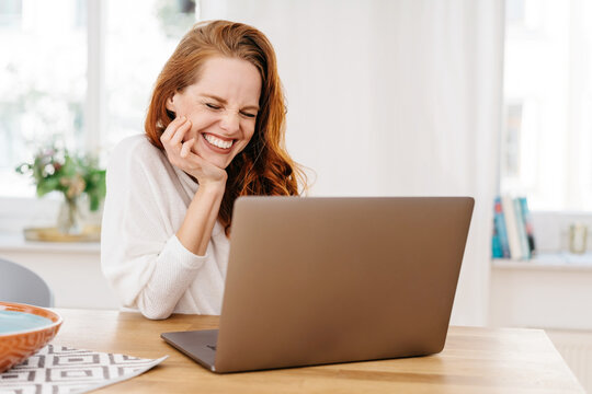 Happy young woman grinning in amusement as she works on a laptop