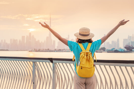 A happy traveler woman with a hat and a yellow backpack enjoys a stunning panoramic view of the Dubai Creek Canal and the famous tallest skyscraper Burj Khalifa