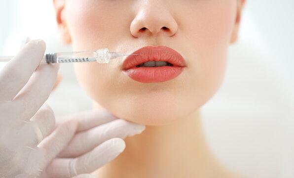 Woman receiving beauty injection in lips