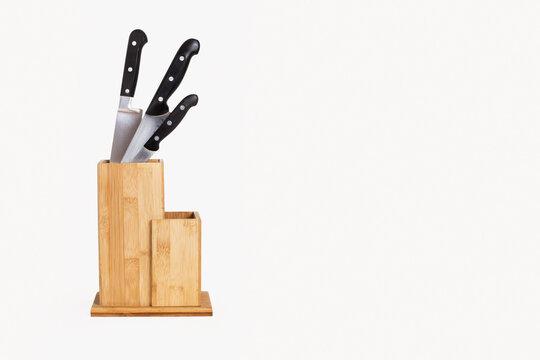 Soporte para cuchillos de madera de Bambú sobre un fondo blanco liso y aislado. Vista de frente. Copy space