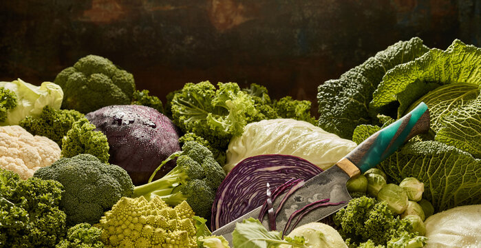 Various cabbages on stall with knife