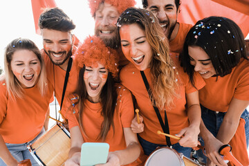Obraz Orange sport supporters watching football game on mobile phone - Betting concept - Main focus on center girl face - fototapety do salonu