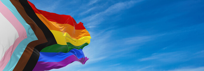 Obraz Progress LGBTQ rainbow flag waving in the wind at cloudy sky. Freedom and love concept. Pride month. activism, community and freedom Concept. Copy space. 3d illustration - fototapety do salonu