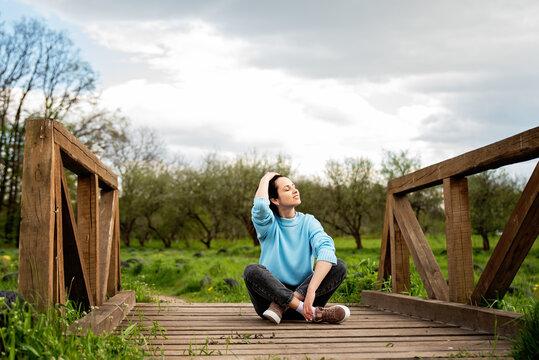 Freedom concept. Enjoyment. Young woman relaxing enjoying fresh air outdoor.