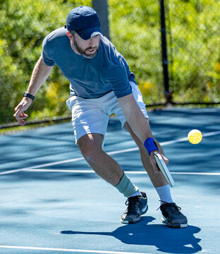 Pickleball player bends low for a volley of the wiffle ball during a tournament