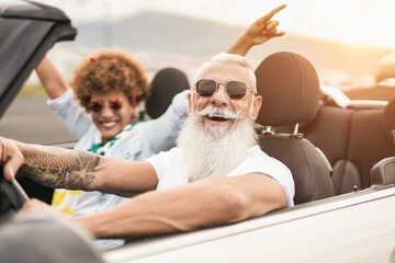 Obraz Happy senior multiracial couple having fun on road trip summer vacation inside convertible car - fototapety do salonu