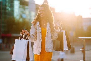 Young woman with shopping bags walking on street. Sale, shopping, tourism and happy people concept.  - fototapety na wymiar