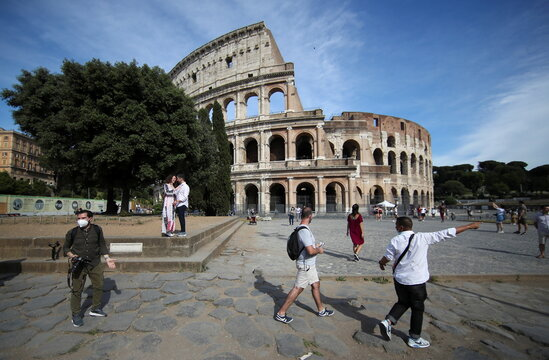 People walk outside the Colosseum, in Rome