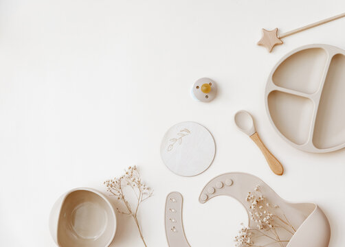 Flat lay beige silicone dishware for baby. Serving kid first feeding concept. copy space, top view