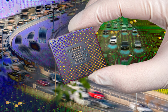 The computer circuit board and fast-moving cars. A hand holding a CPU chipset.