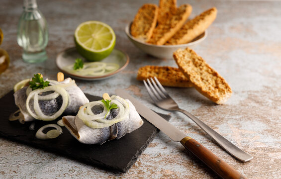 pickled herring on a plate. Seafood, pickled herring marinated in vinegar and onions on a plate. Served on a old wooden table top. Top view.