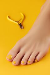 Fototapeta Manicure, pedicure beauty salon concept. Womans foot with clippers on orange background obraz
