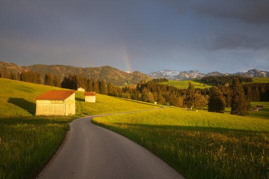 Allgäuer Straße mit Regenbogen und Berge