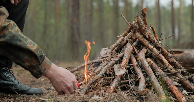 Man starts a fire in the forest using a lighter. Close-up of a man's hand lighting a fire with a lighter. Lighting a fire in the forest by a person. Low angle of a burning fire made of brushwood...