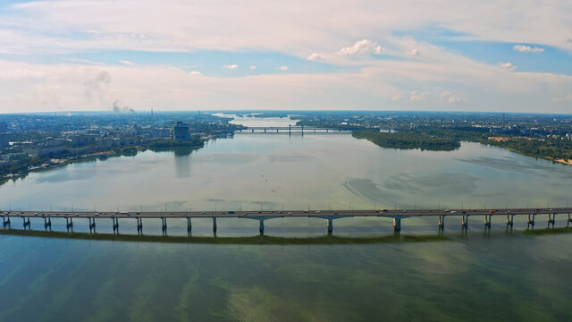 Aerial photo - Beautiful city landscape with a river. Photo of a beautiful long bridge over the river from the throne. Urban environment with a wide river.