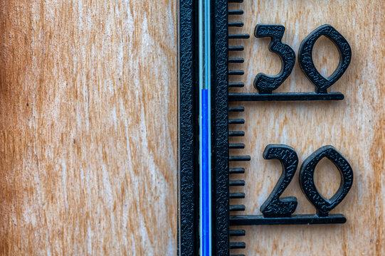 Thermometer mit sommerlichen Temperaturen auf hölzernem Hintergrund